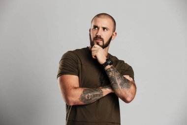 Portrait of manly bald guy with tattoo on his arms looking aside