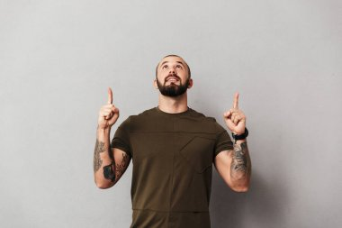 Image of bearded man with tattoos on arms looking upward with po