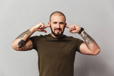 Picture of handsome guy with beard and mustache plugging his ear