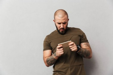 Bearded man 30s in casual clothes playing games on smartphone, i