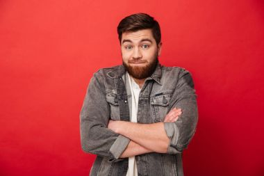 Photo of bearded man in jeans jacket shrugging and expressing no