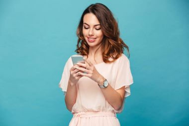 Contented smiling woman typing text message or scrolling through