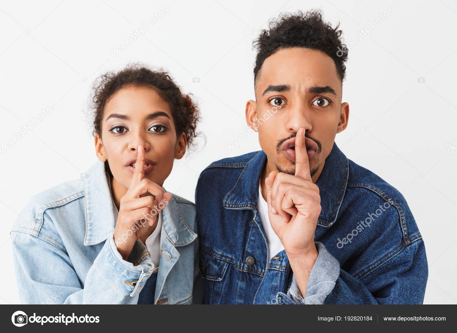Africká pár tajemství v džínové košile ukazující mlčení gesta při pohledu  na fotoaparát šedé pozadí — Fotografie od ... 37ef333f8e