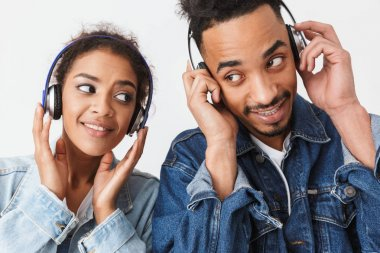 Pleased african couple in denim shirts listening music by headphones