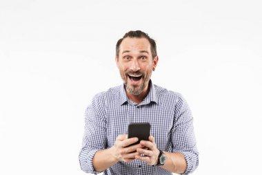 Surprised emotional adult man using mobile phone.