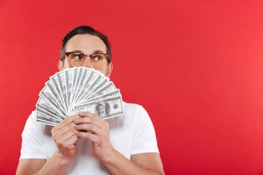 Photo of successful man in casual white t-shirt covering face with lots of money in dollar bill holding in hands and looking aside on copyspace isolated over red wall stock vector