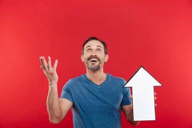 Photo of pleased guy 30s holding blank speech arrow pointer dire