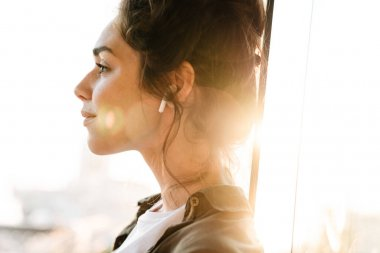 Image of lovely brunette woman listening to music with earpods o