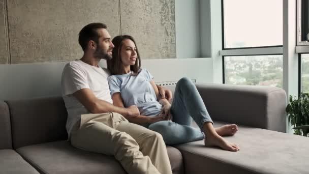 Krásný mladý krásný pár objímání a mluvení při pohledu na okno sedí na pohovce doma
