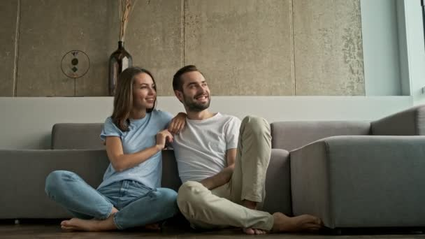 Attractive cheerful young lovely couple hugging and looking to the side at the window while sitting on the floor near the couch at home