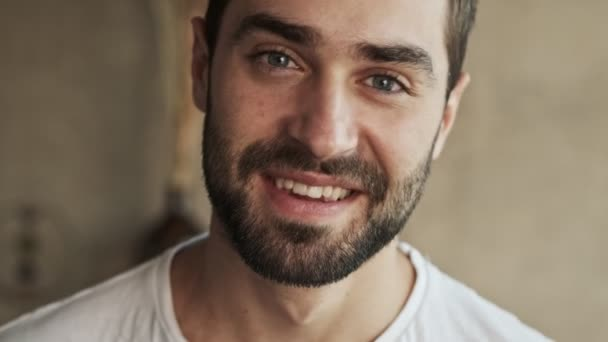 Zblízka pohled na krásné veselý mladý brunet muž usmívá a směje se při pohledu na kameru doma