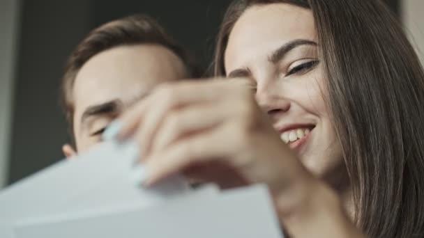 Vágott kilátás vonzó fiatal szép pár nézi a családi portrék és mosolyog, miközben otthon ül