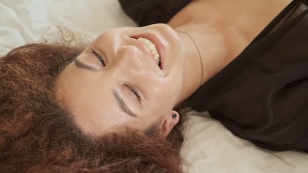 Cropped view of attractive cheerful young redhead woman in silk robe smiling and laughing while lying in bed at home in the morning