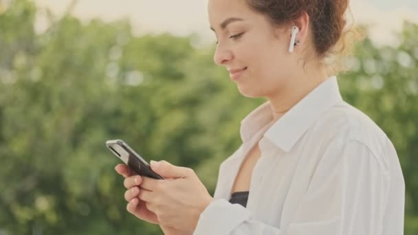 Side view of cute smiling young redhead woman in white shirt chatting on smartphone and listening music with wireless earphones while resting in the park