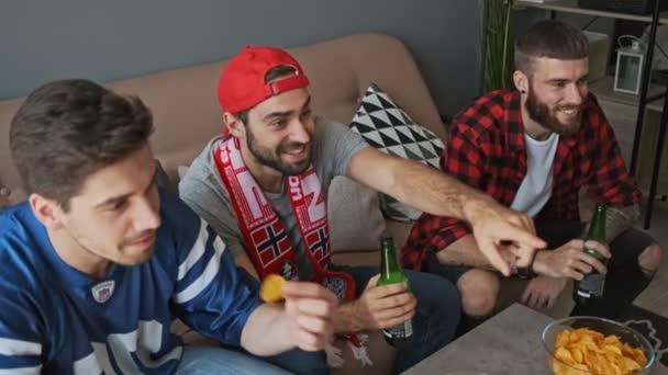 Drei glückliche Männer, die Spaß haben und Bier trinken, während sie auf etwas zeigen und in der Wohnung Sport gucken