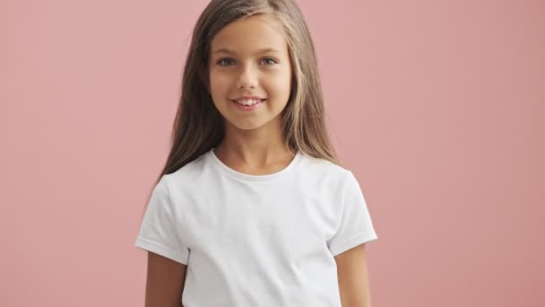 Happy little girl looking at the camera and smiling over pink background isolated
