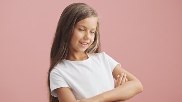 Boldog kislány összecsukott kézzel néz a kamerába, és mosolyog át rózsaszín háttér elszigetelt