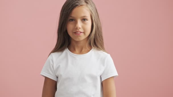 Smiling little girl looks at the camera over pink background isolated