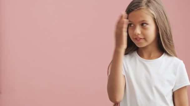 Smiling little girl looking camera holding copy space on the palm and pointing on this over pink background isolated