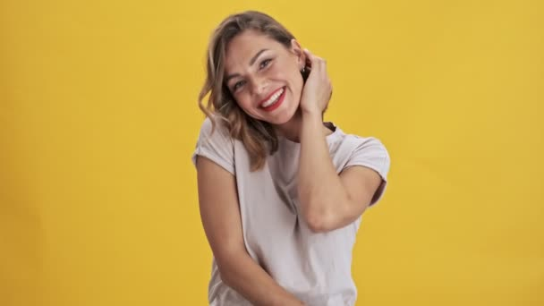 Charming young woman with red lips smiling and touching her hair and embarrassing while looking at the camera over yellow background isolated