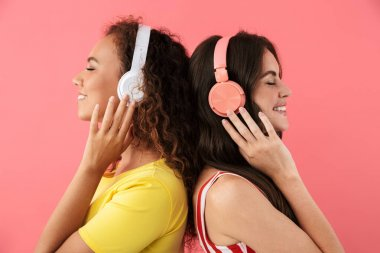 Image of charming multinational girls listening to music with headphones