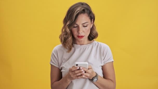 Pěkná žena s červenými rty cheking její telefon a usmívat se přes žluté pozadí izolované