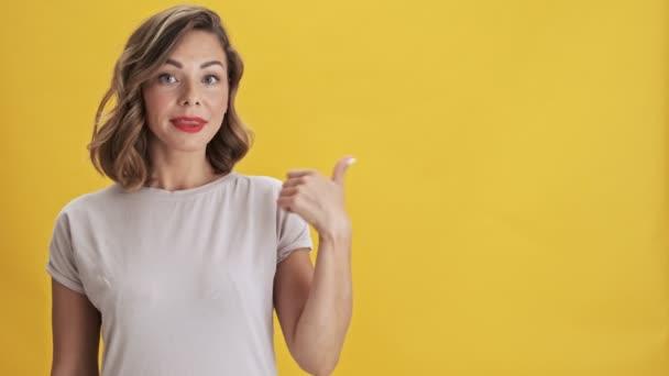 schöne junge Frau mit roten Lippen lächelt und zeigt mit dem Finger zur Seite und macht Daumen nach oben Geste in einem anderen, während Blick in die Kamera über gelbem Hintergrund isoliert