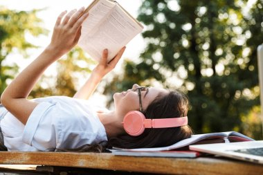 Lady listening music with headphones on copybooks reading book.