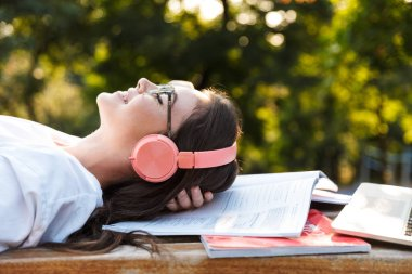 Lady outdoors listening music with headphones on copybooks.
