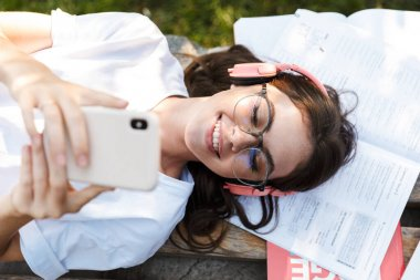 Lady listening music with headphones on copybooks using mobile phone.