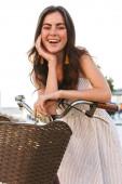 Krásná usměvavá dívka nosí letní šaty na koni