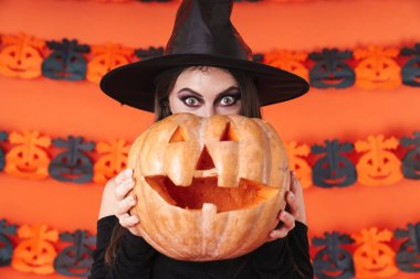 Image of witch girl in black halloween costume holding carved pu