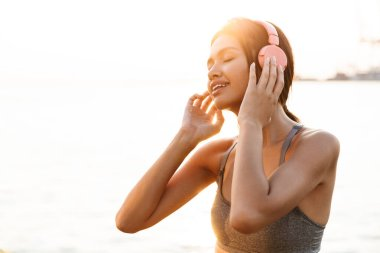Image of happy asian woman listening to music with headphones by