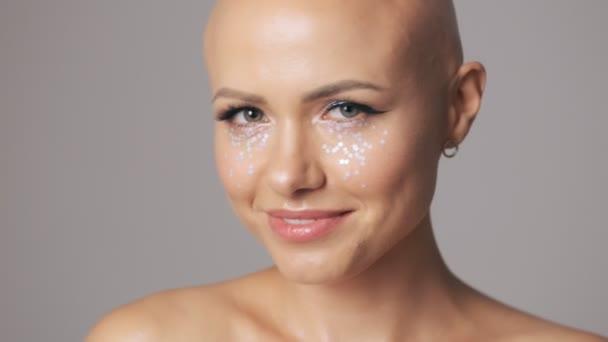Oříznutý pohled na atraktivní mladé holé ženy s módní oční make-up poslat vzduchový polibek při pohledu do kamery izolované přes šedou stěnu