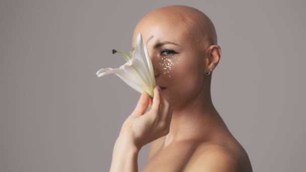 Nice young hairless woman with fashion eye makeup playing with white lily bud while moving it diagonally isolated over gray wall