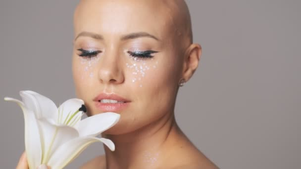 Omračující mladá bezsrstá žena s módní oční make-up při pohledu na bílé lilie bud a zároveň ji drží v ruce izolované přes šedou stěnu