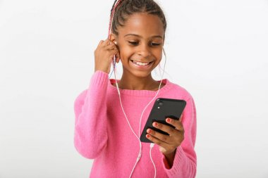 Image of cheerful african american girl using cellphone and earphones