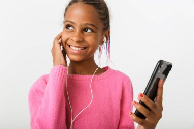 Image of pleased african american girl holding cellphone and earphones