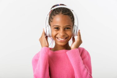 Image of pleased african american girl listening music with headphones