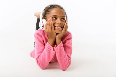 Image of cheerful african american girl listening music with headphones
