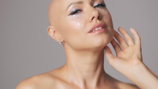Hezké mladé vlasy žena s módní oční make-up pózování při pohledu do kamery izolované přes šedou stěnu