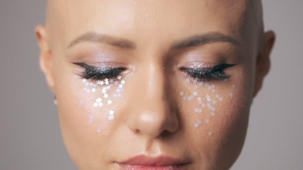 Közelről kilátás fiatal szőrtelen nő divat szem smink nyitja a szemét, hogy a kamera elszigetelt szürke fal