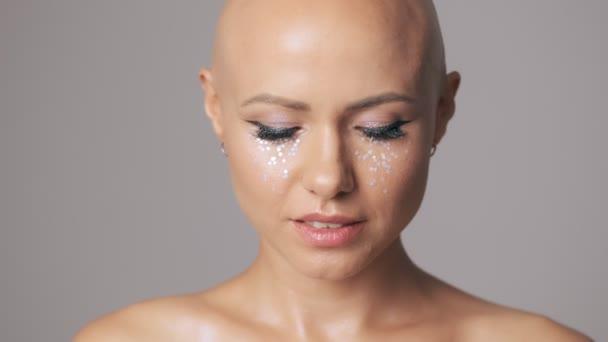 Atraktivní mladá žena bez chlupů s módní oční make-up otevření očí do kamery izolované přes šedou stěnu