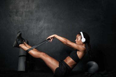 Image of concentrated african american woman doing workout with expander
