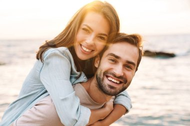 Image of young happy man giving piggyback ride beautiful woman