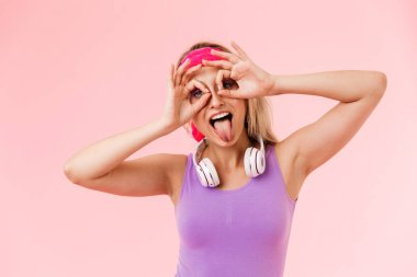Image of nice amusing woman grimacing with headphones over neck