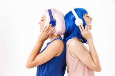 Portrait of two pleased women wearing blue and pink wigs listening music with headphones back to back