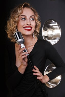 Image of caucasian vocalist woman in elegant dress singing into microphone