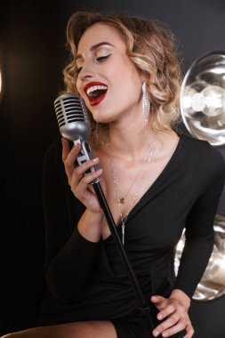 Image of blonde vocalist woman in dress singing into microphone