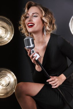 Image of gorgeous vocalist woman in dress singing into microphon